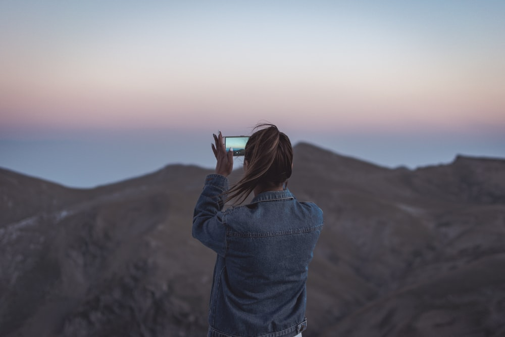woman in blue denim jacket taking picture of mountain