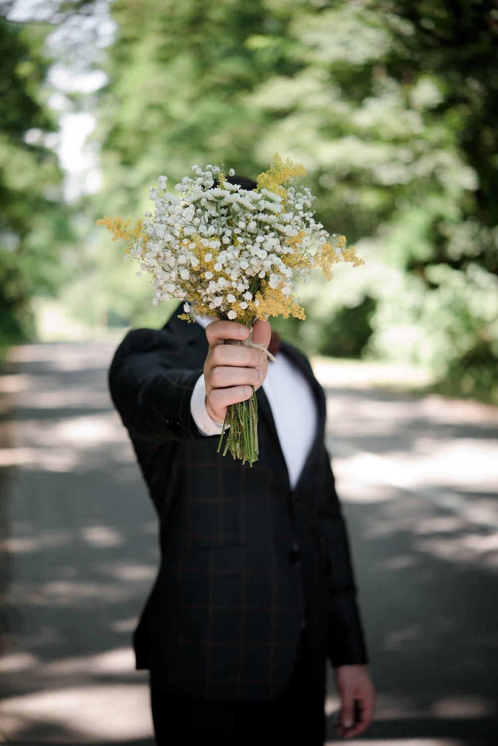 selective focus photo of man wearing black suit jacket holding flower bouquet