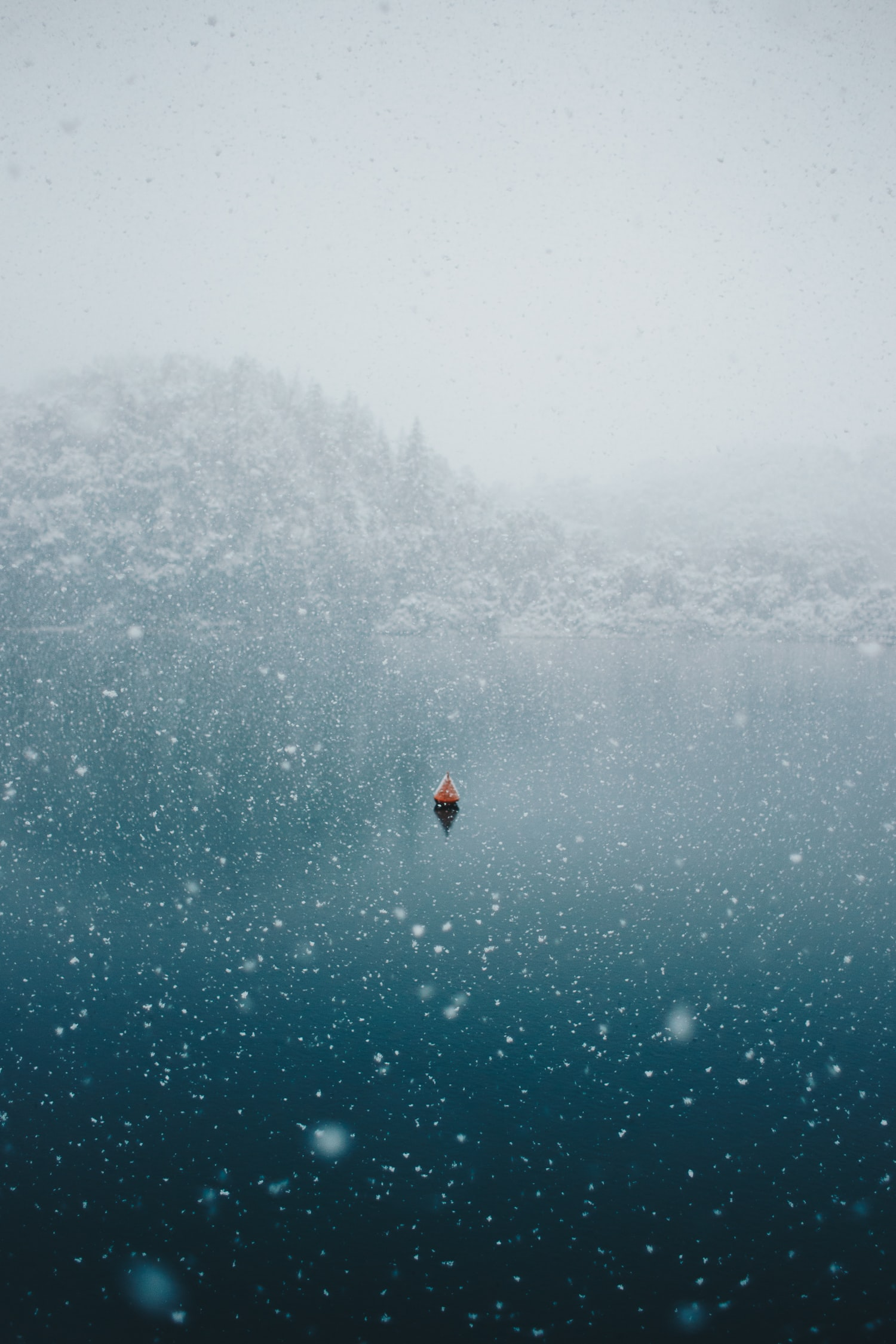 Snowing over an ocean with a lone boat.