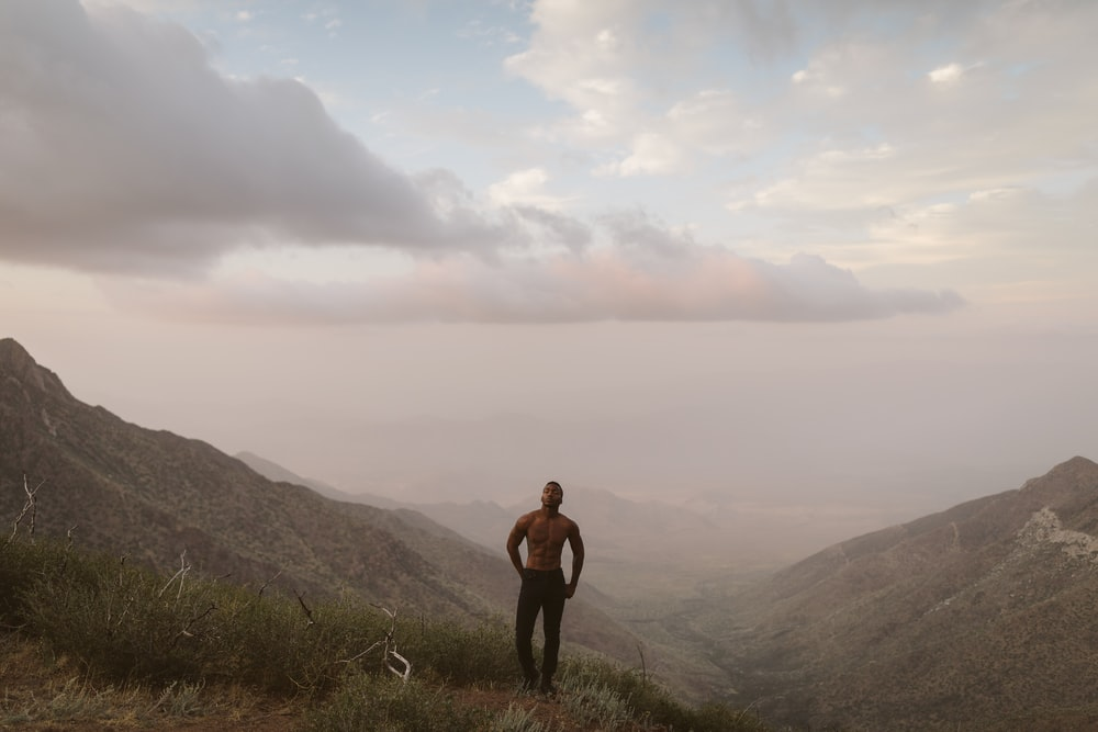man standing on mountain peak under white clouds