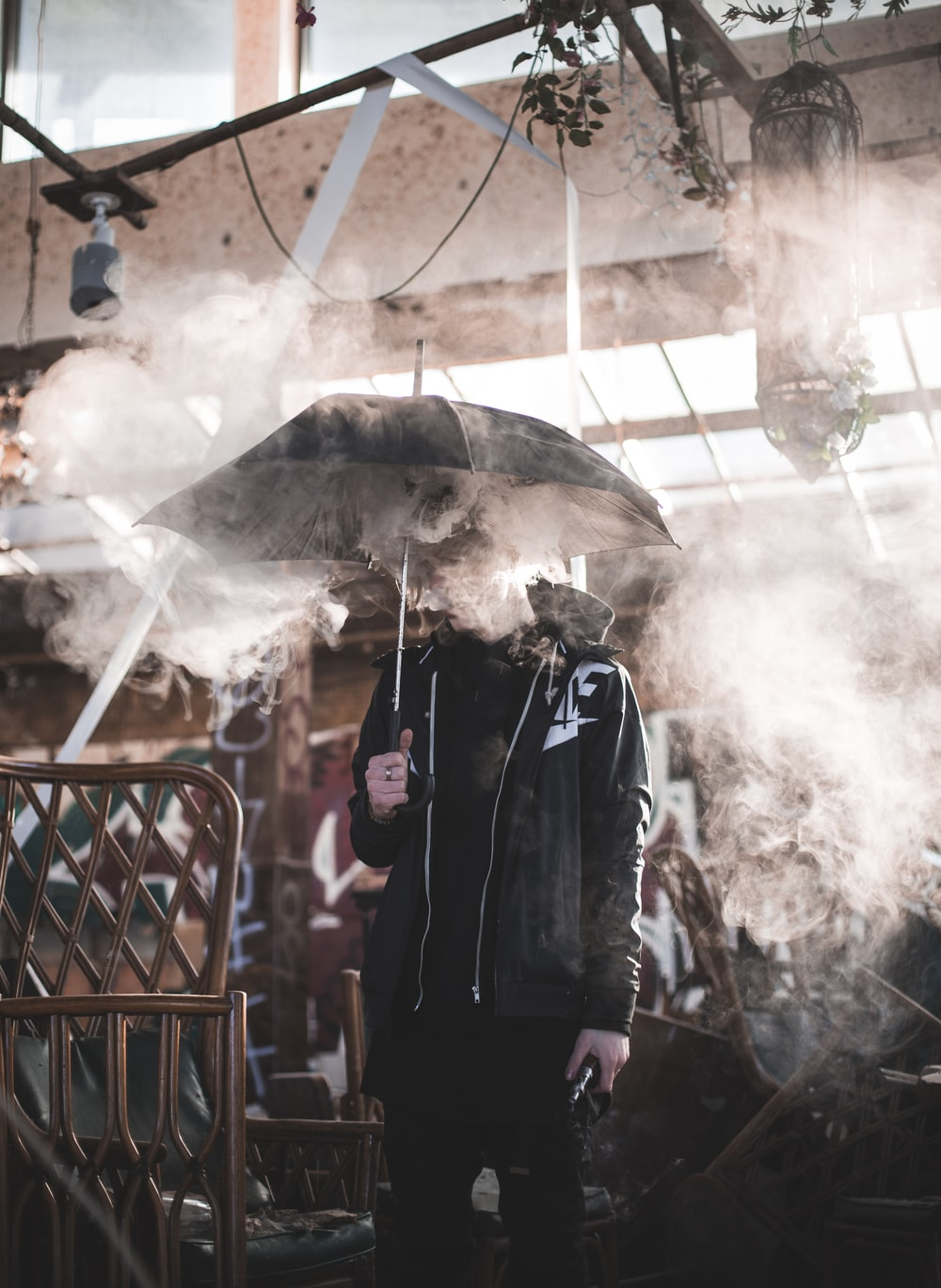 man holding a black umbrella covering him with smoke