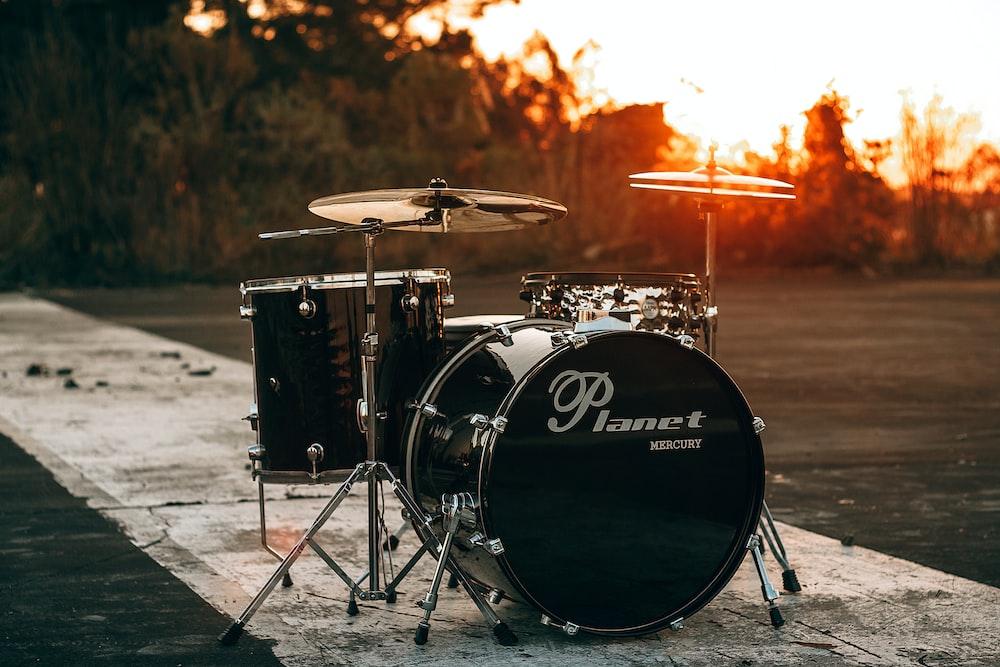 black Planet drum kit near trees during sunset