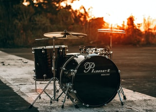 black Planet drum kit near trees during sunset
