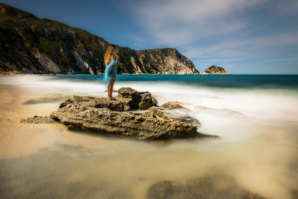 woman standing on rock at beach during daytime
