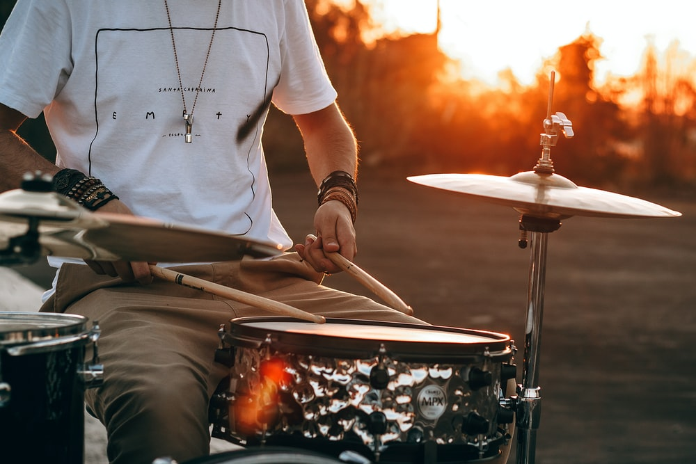person playing drum during golden hour
