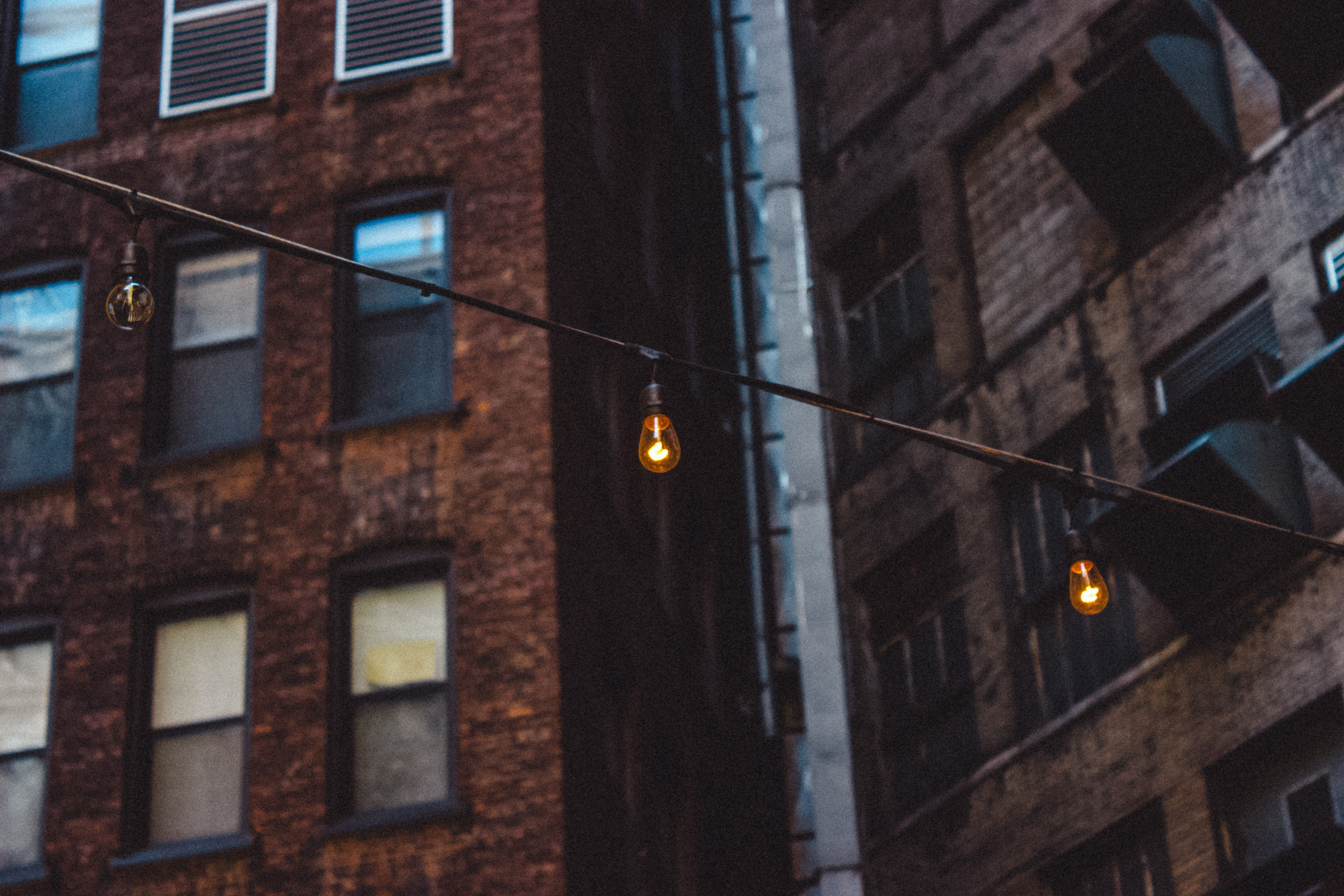 lighted string of light bulbs mounted on buildings outdoors