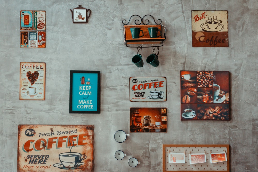 assorted-color coffee and quote wall decors on wall