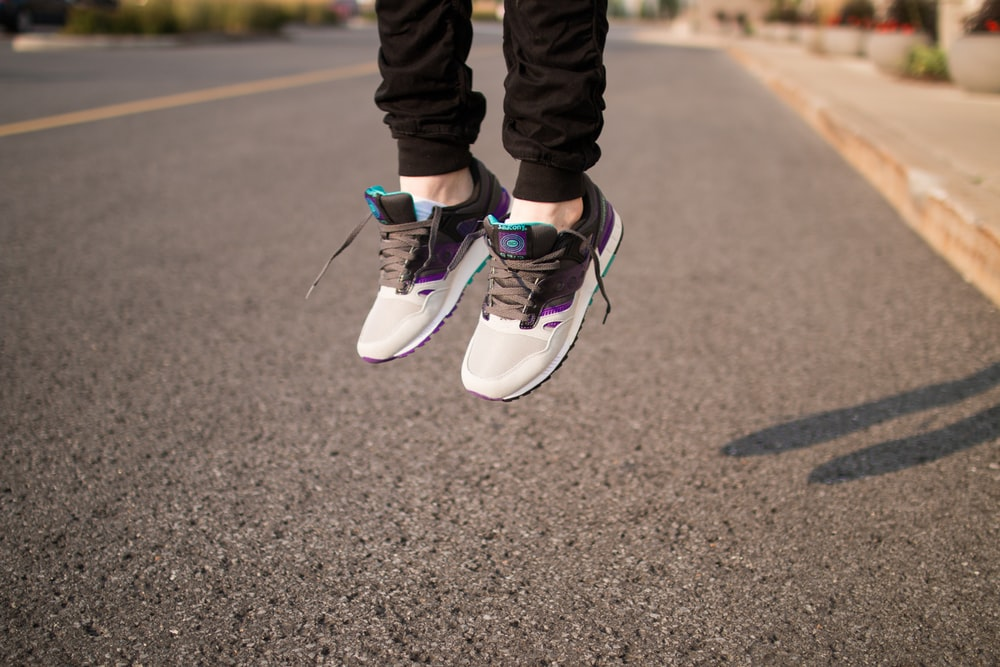 person wearing white and gray sneakers jumping over gray roadway