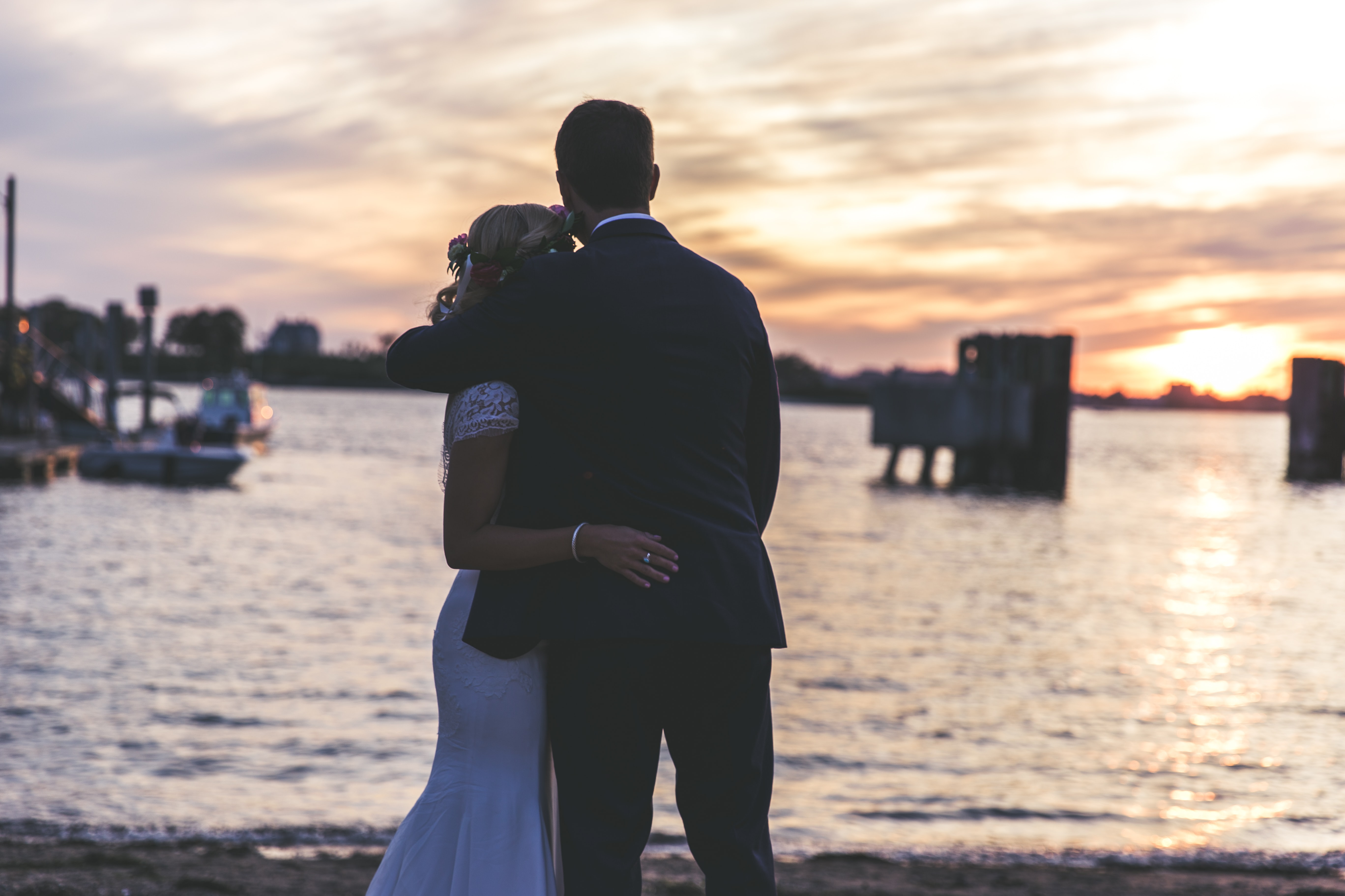 bride and groom hugging near seashore