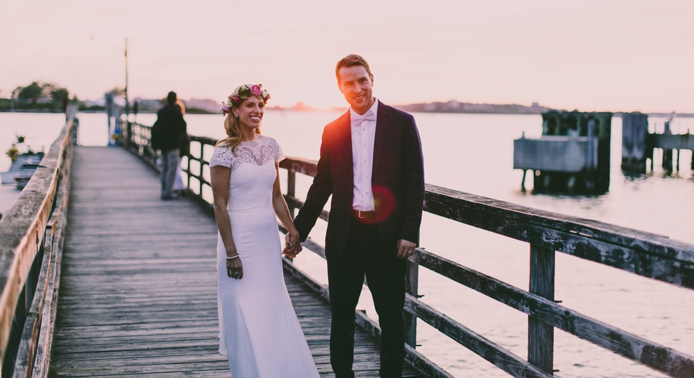 bride and groom standing on wooden dock near body of water