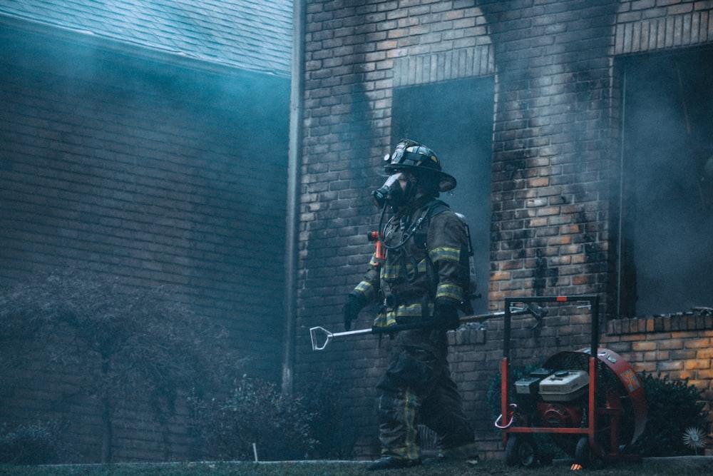 fireman holding rod near building at daytime