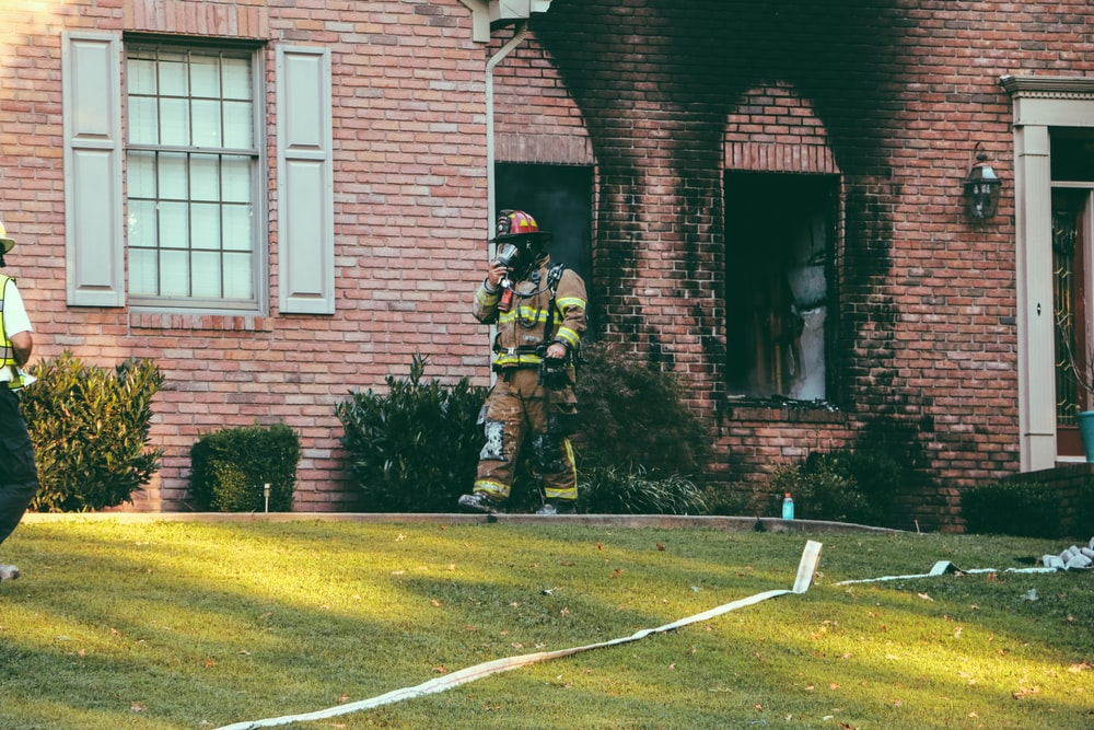 fireman walking in front of brown brick house