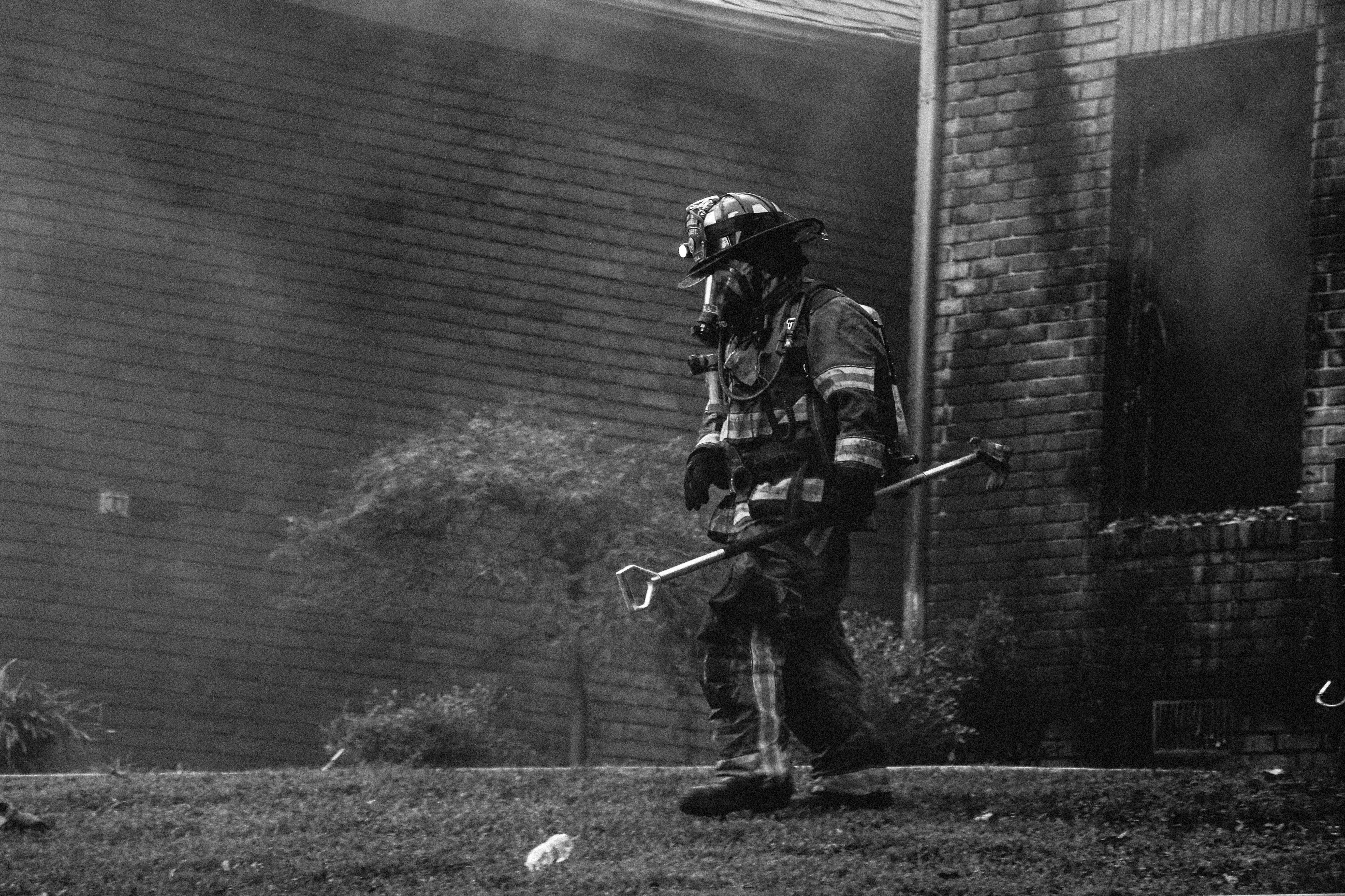grayscale photography of firefighter holding equipment near houses