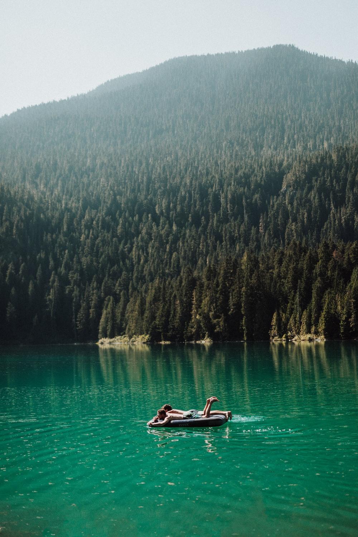 men lying on floater on lake