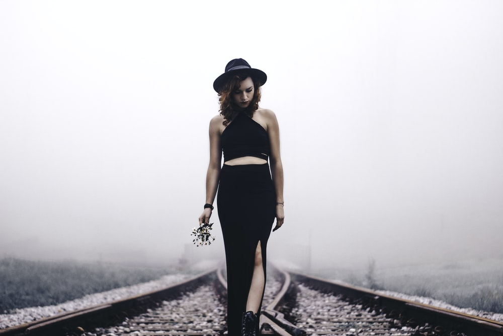 woman holding flowers looking on train rails