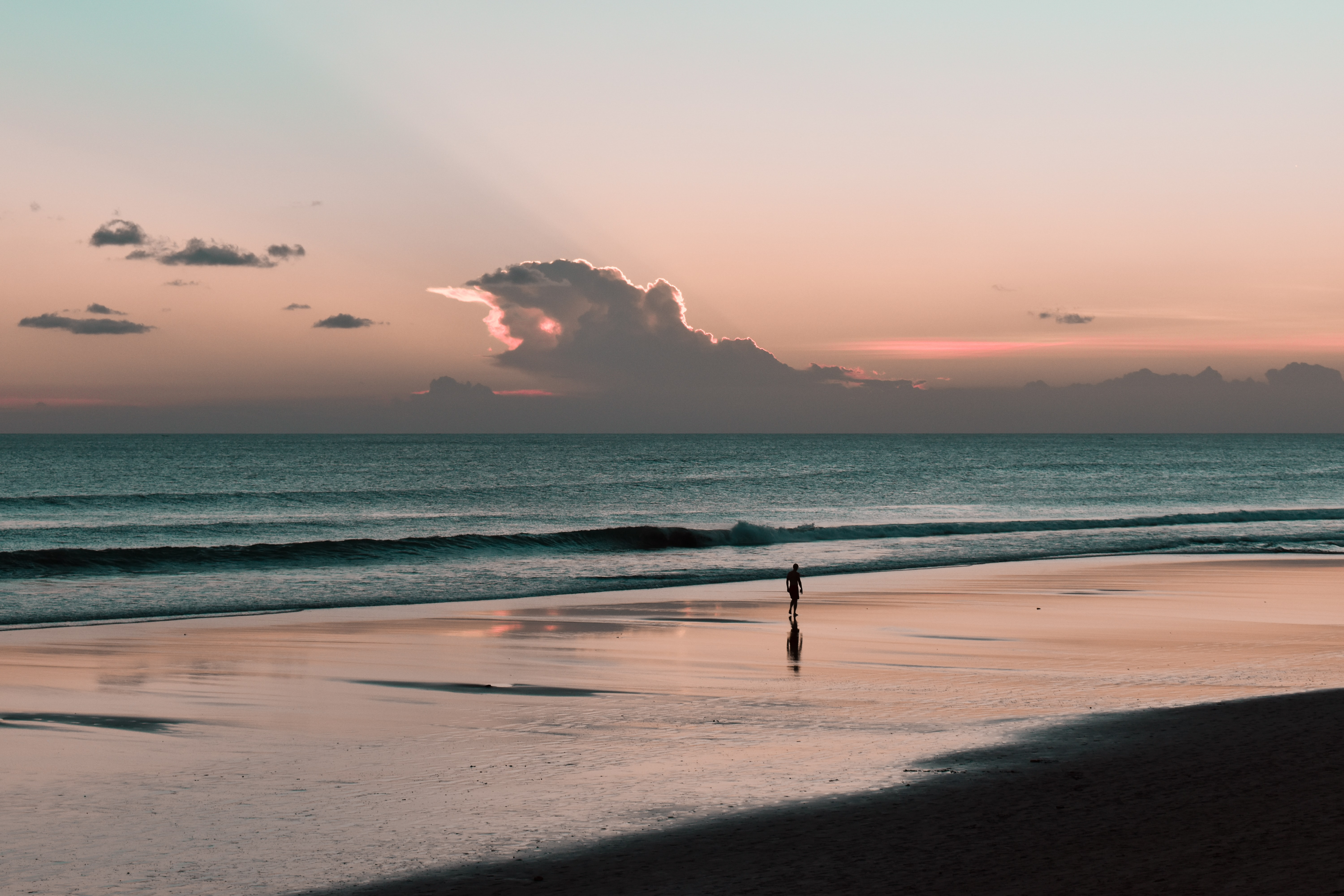 silhouette of person facing body of water on seashore