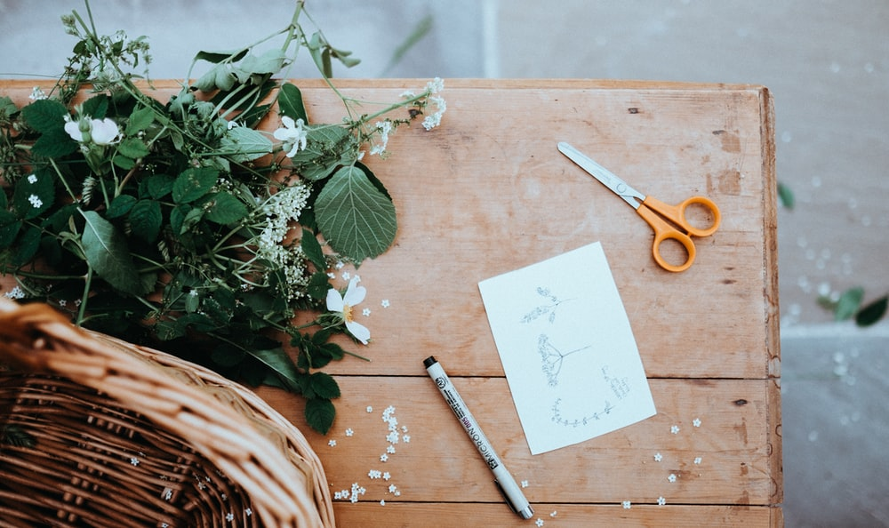 orange and gray scissors on table