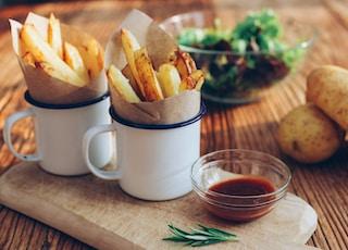 potato fries on mugs beside sauce