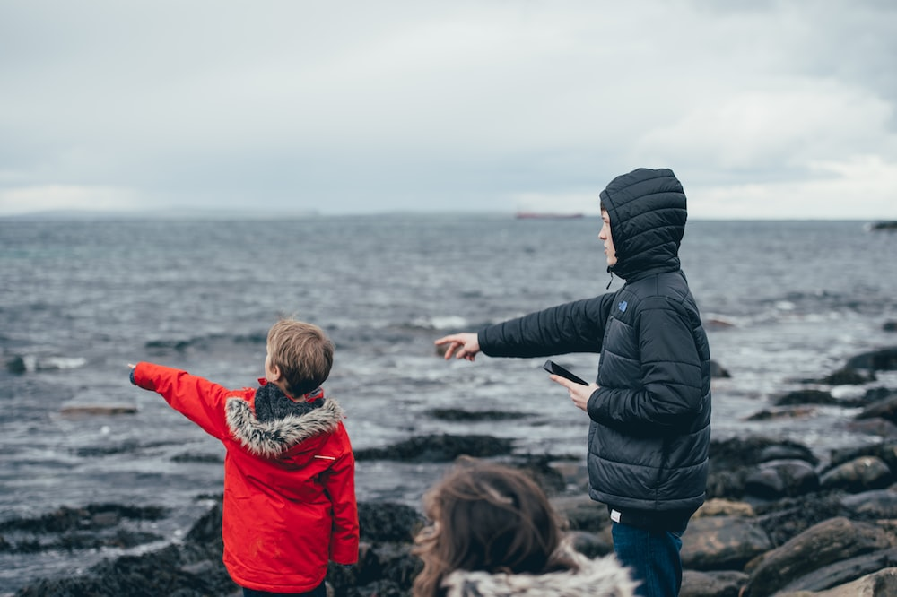 boy and man pointing on sea taken under white clouds during daytime