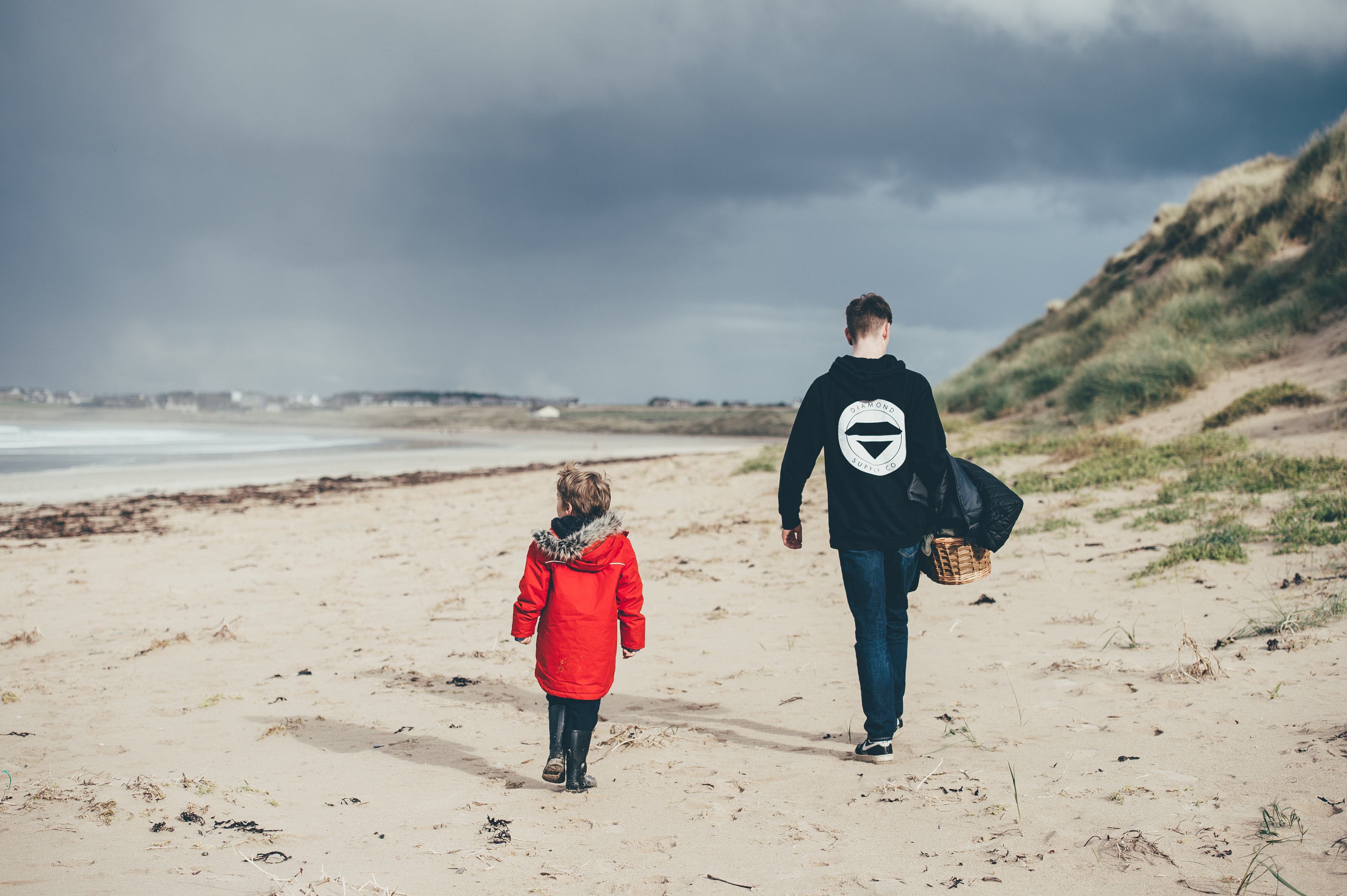 man and girl walking on beach