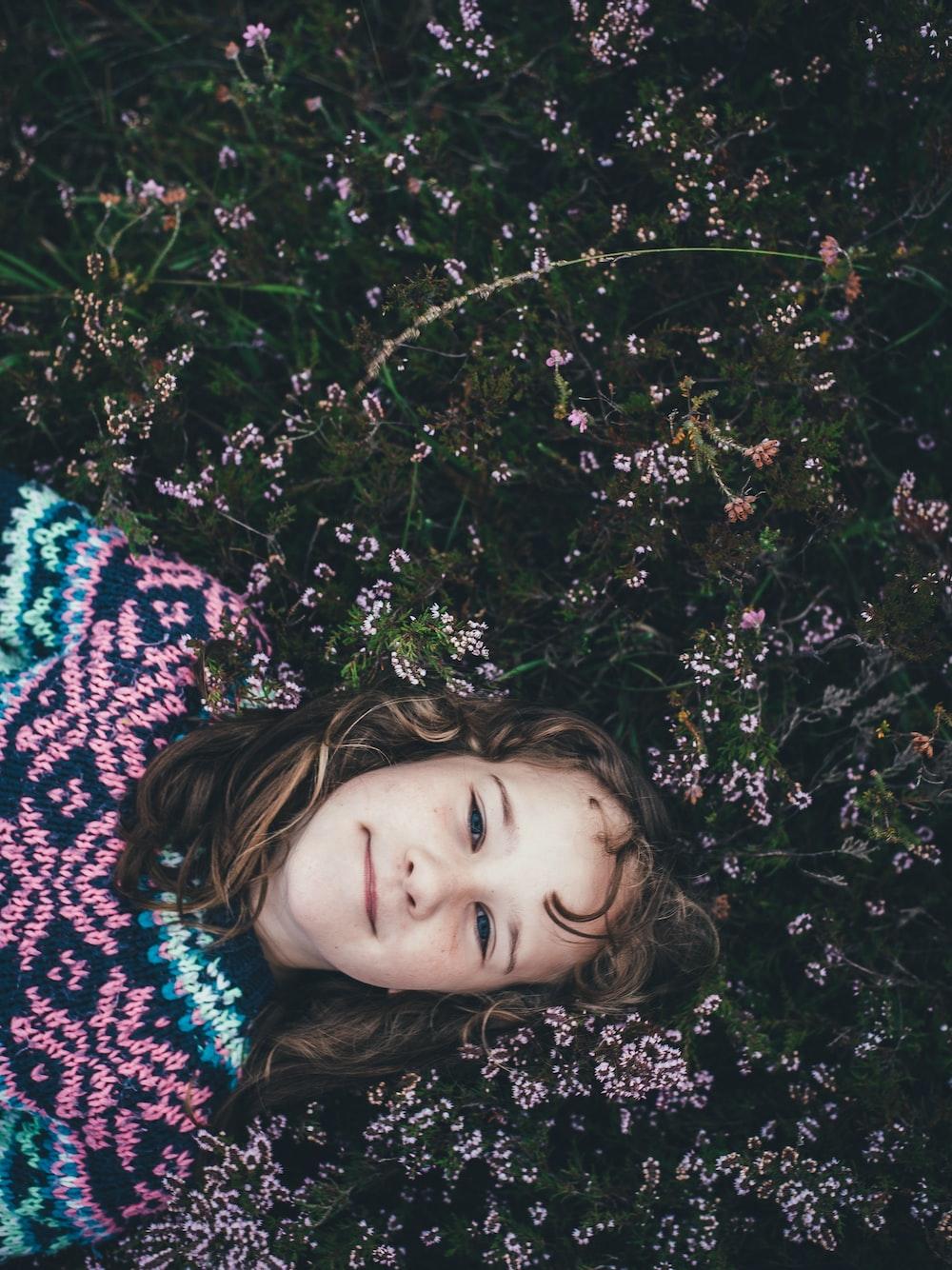 girl lying on pink petaled flowers