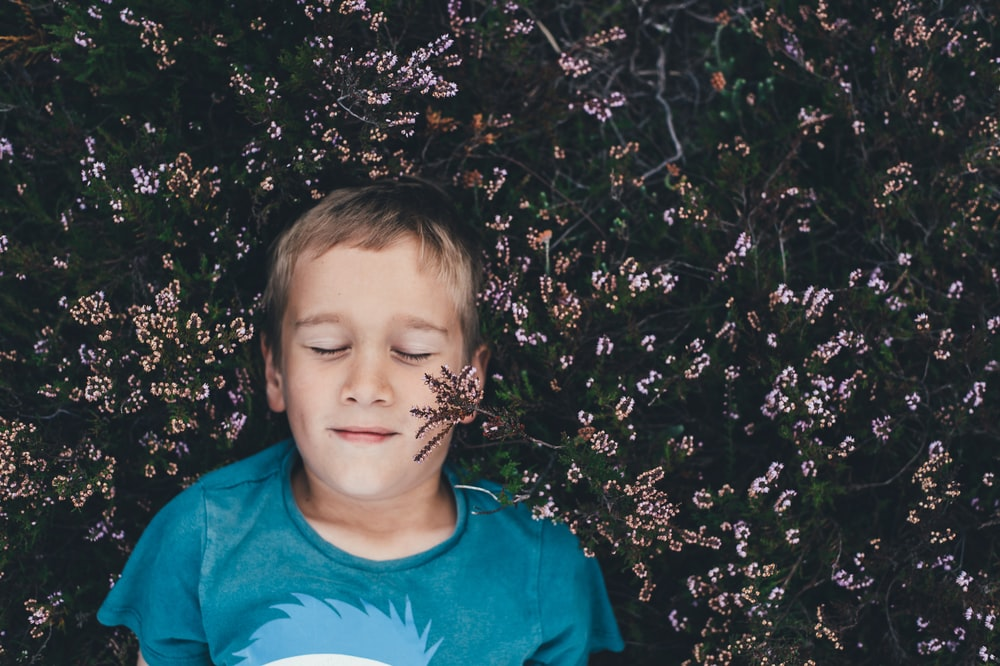 boy on teal shirt lying on pink flowers