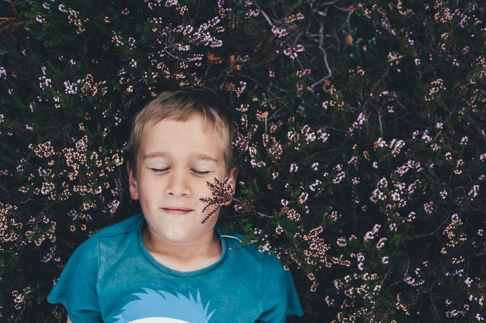 boy on teal shirt lying on pink flowers