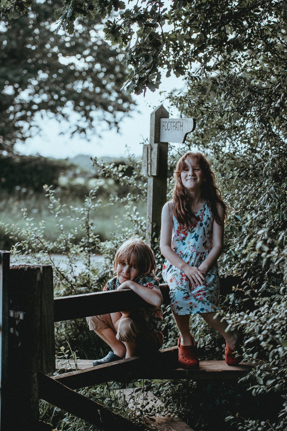 photo of two boy and girl sitting on bench