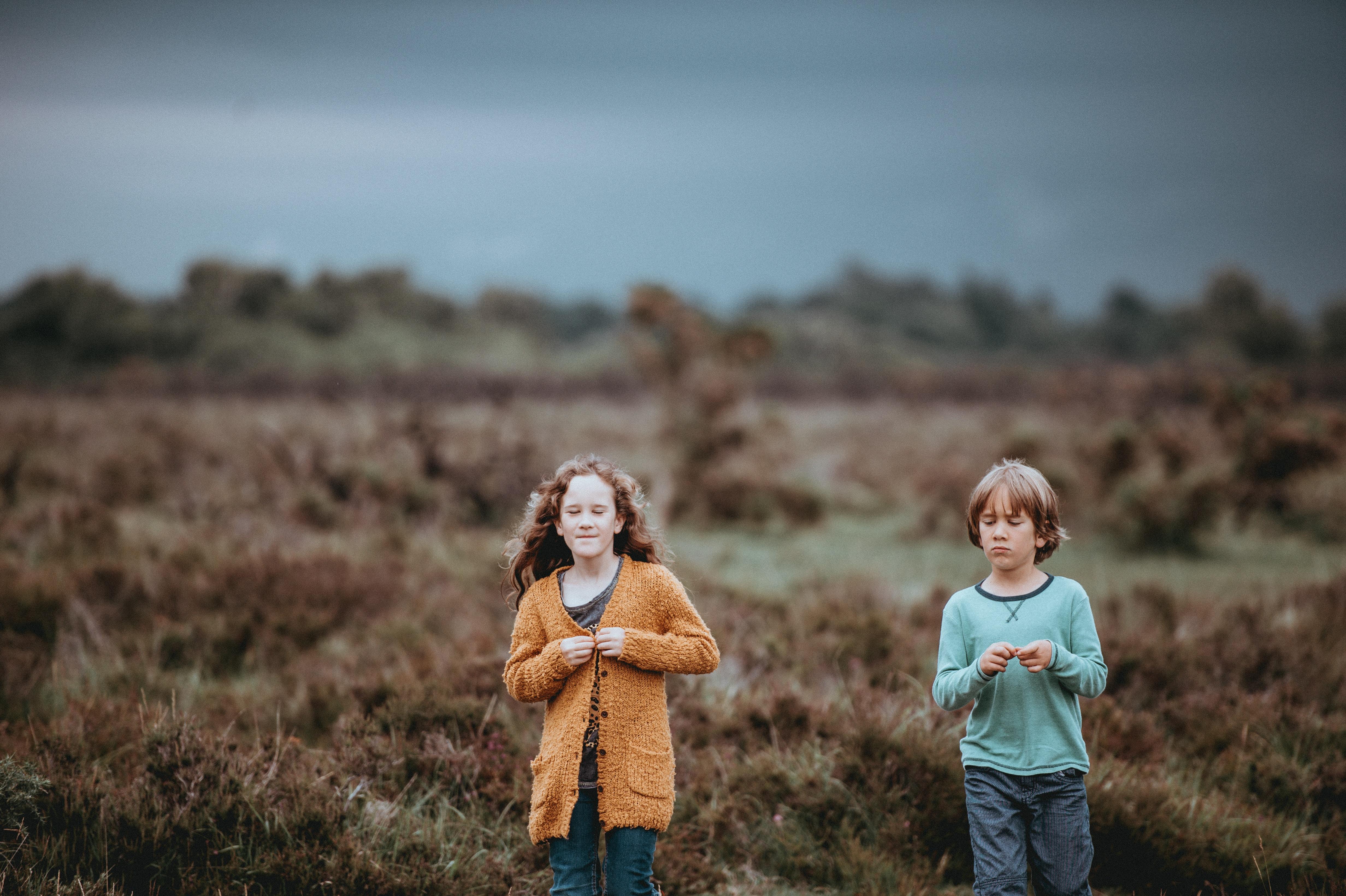 shallow focus photography of children walking