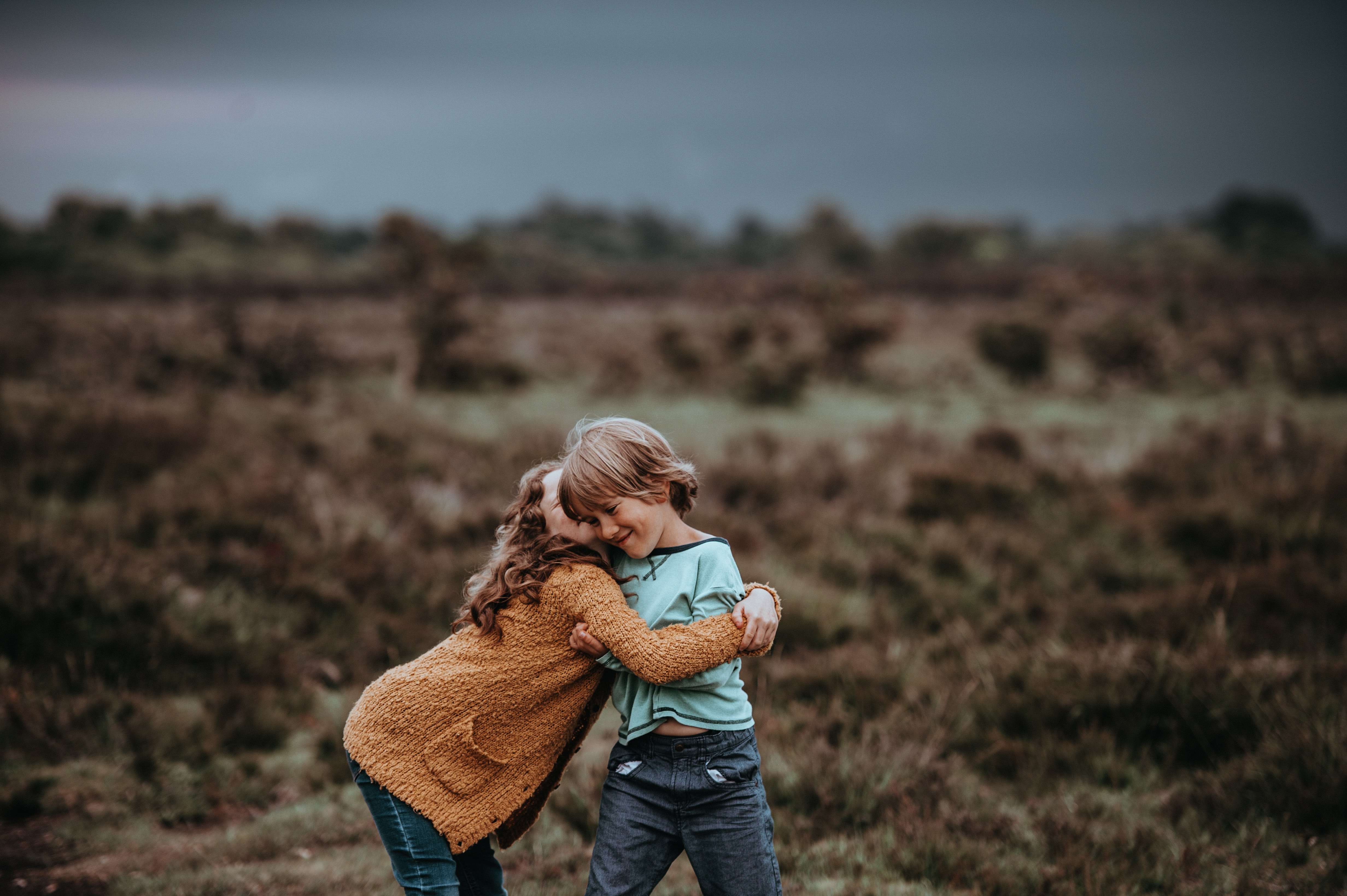 two child hugging in front of field