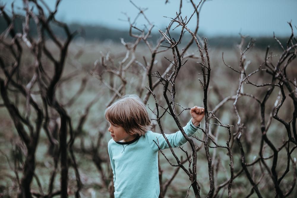 boy wearing teal long-sleeved shirt beside leafless tree