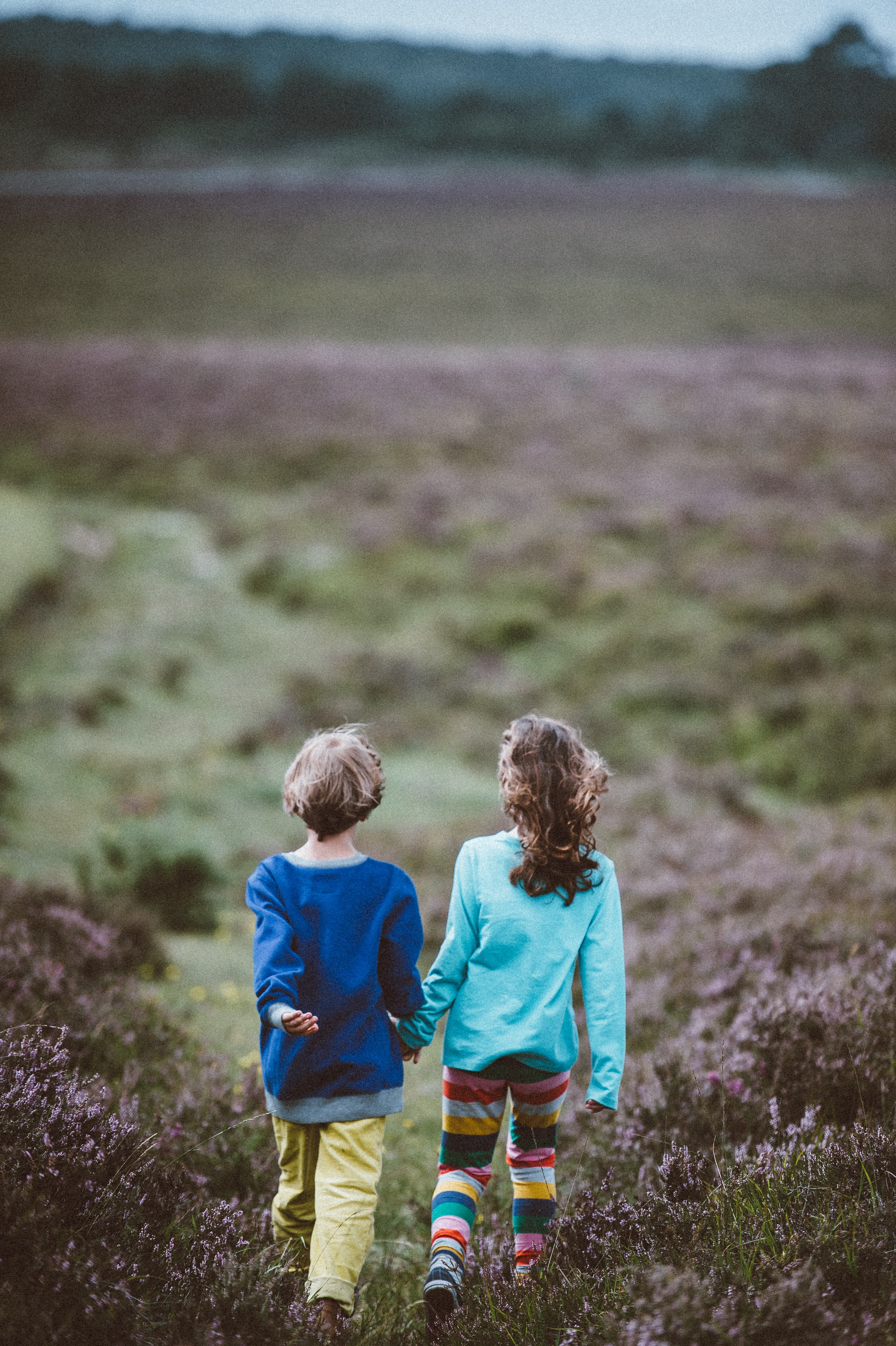 boy and girl holding each others hand while walking on field