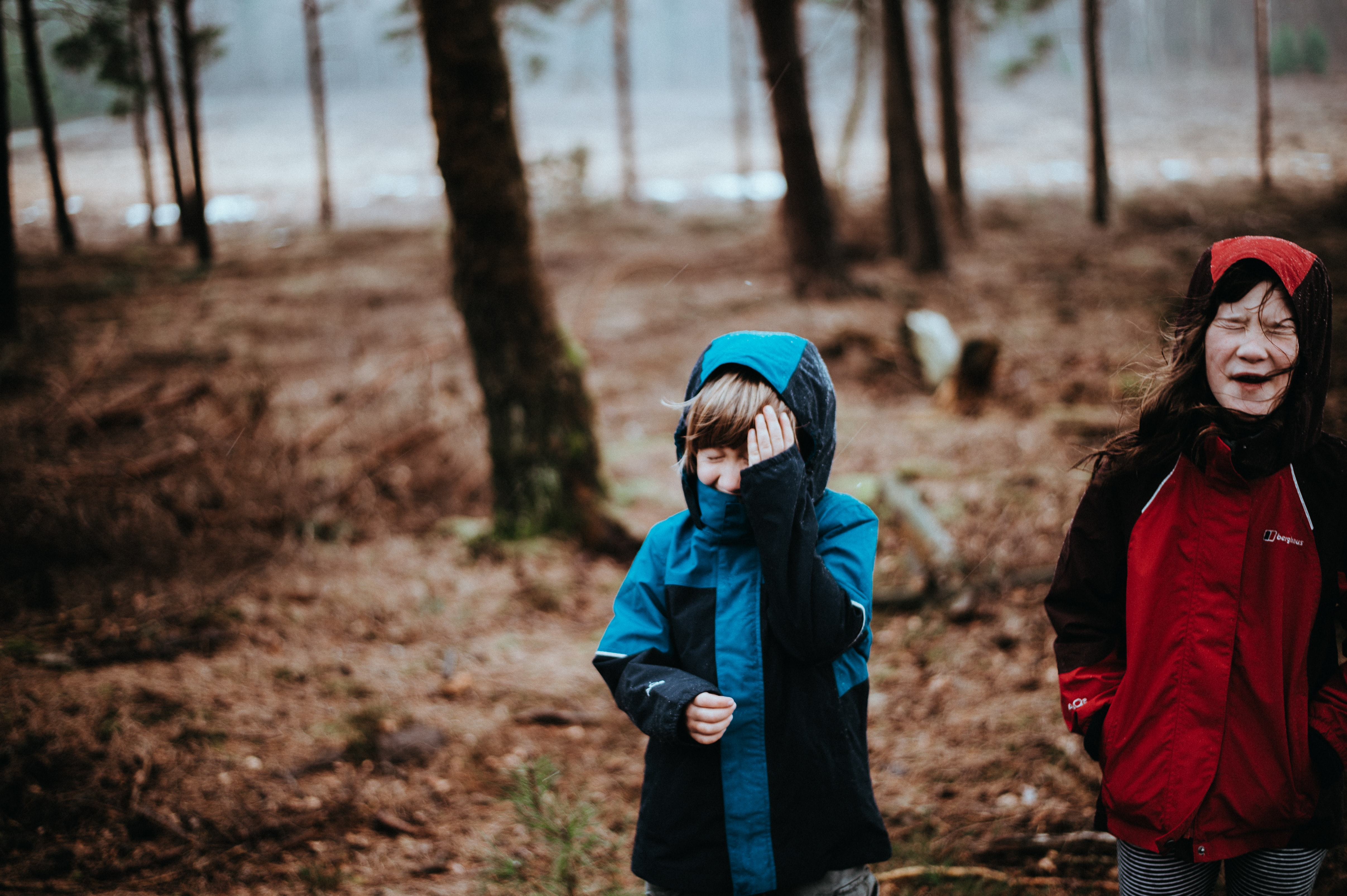 two children wearing blue and red coats standing on woods