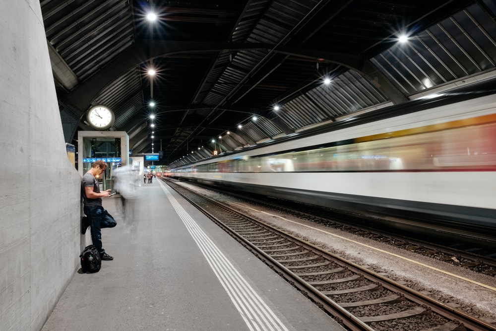 man standing in train station time lapse photography