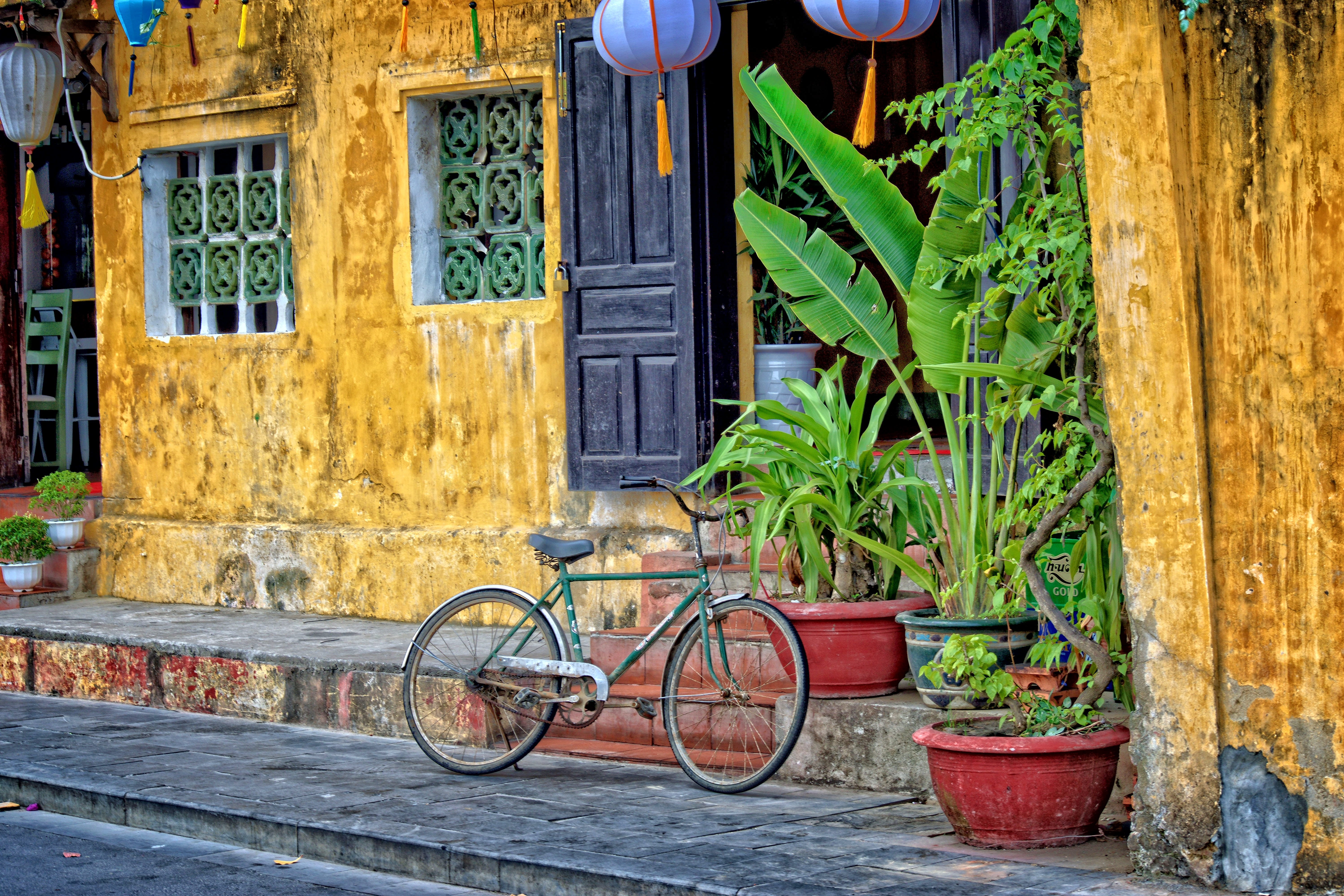 green bicycle parked beside yellow concrete house at daytime