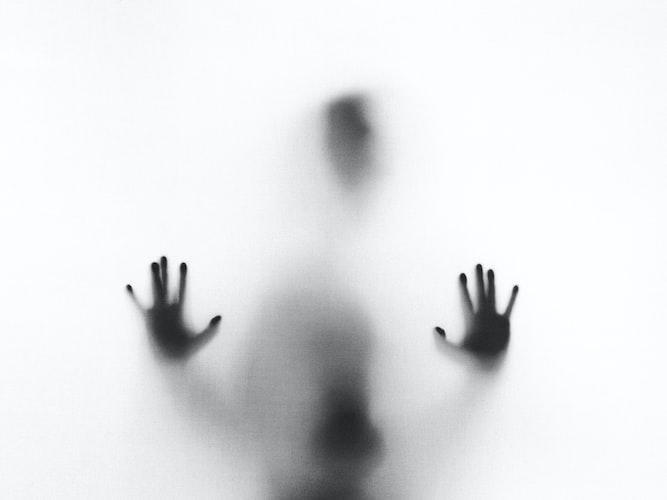 Persona sfocata dietro a un vetro con le mani spalmate su di esso in evidenza