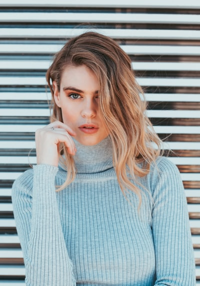 woman wearing gray turtle-neck top standing near white wall