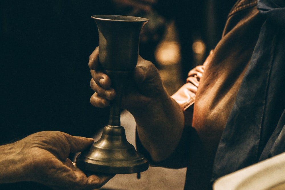person holding gold chalice