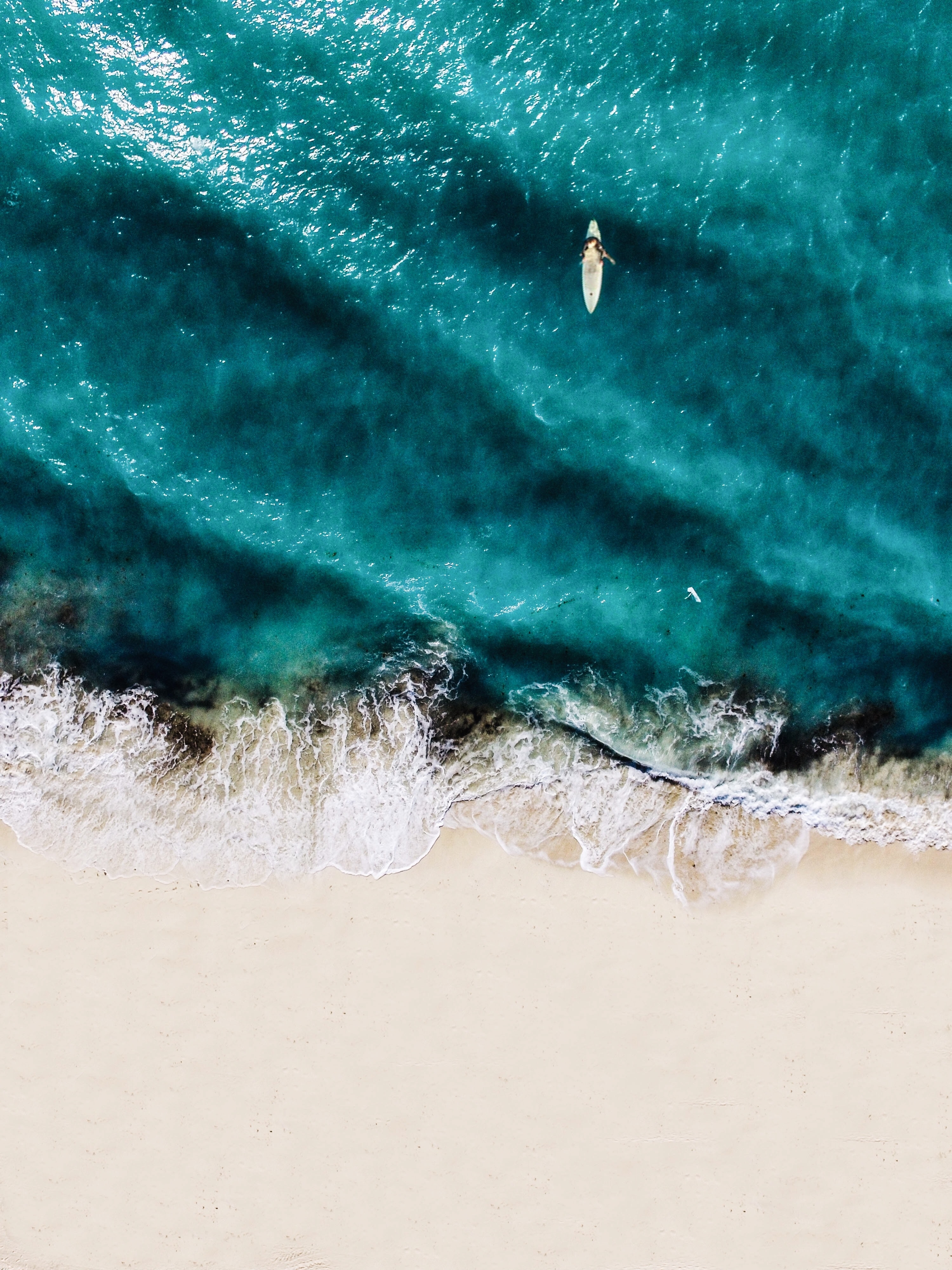 aerial photography of person doing surfboard on body of water at daytime