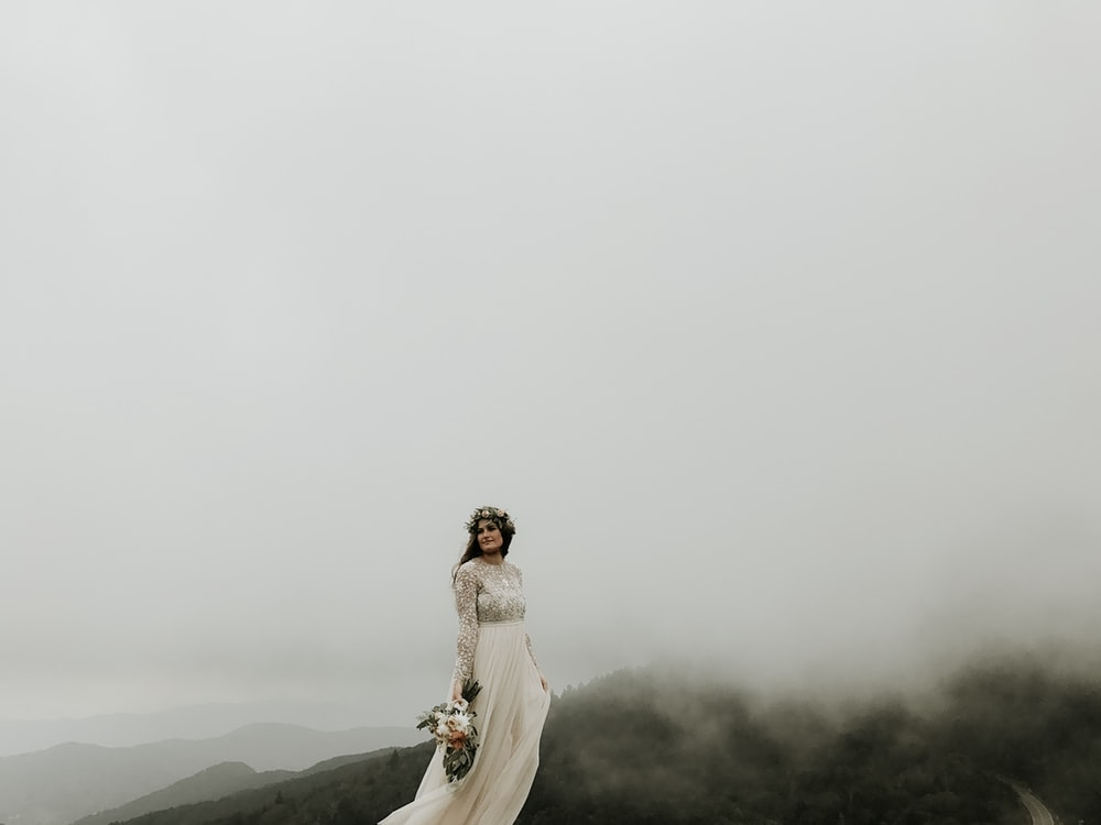 woman wearing wedding gown standing on top of hill