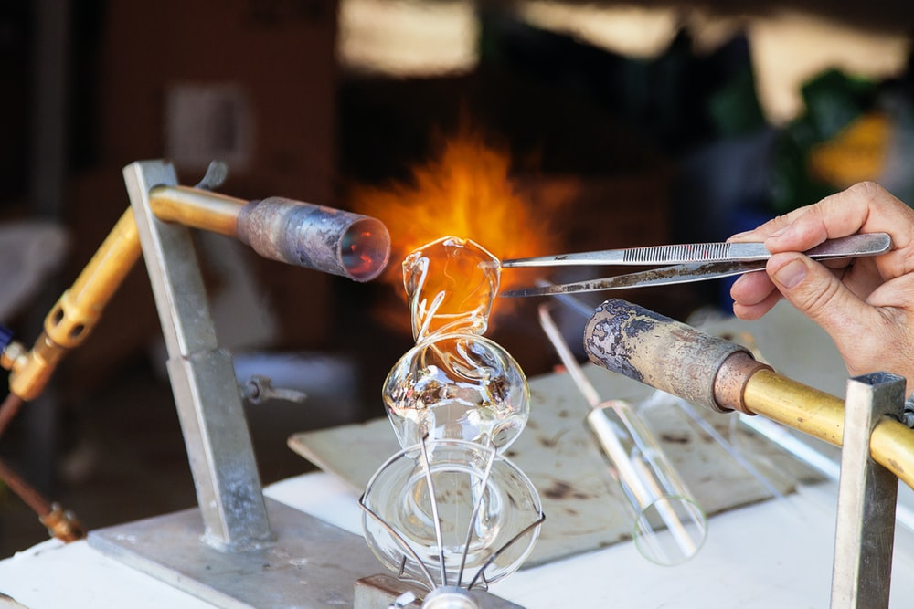 person molding glass vase through blowtorch