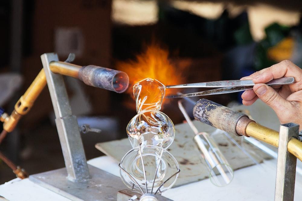 person molding glass vase through blowtorch