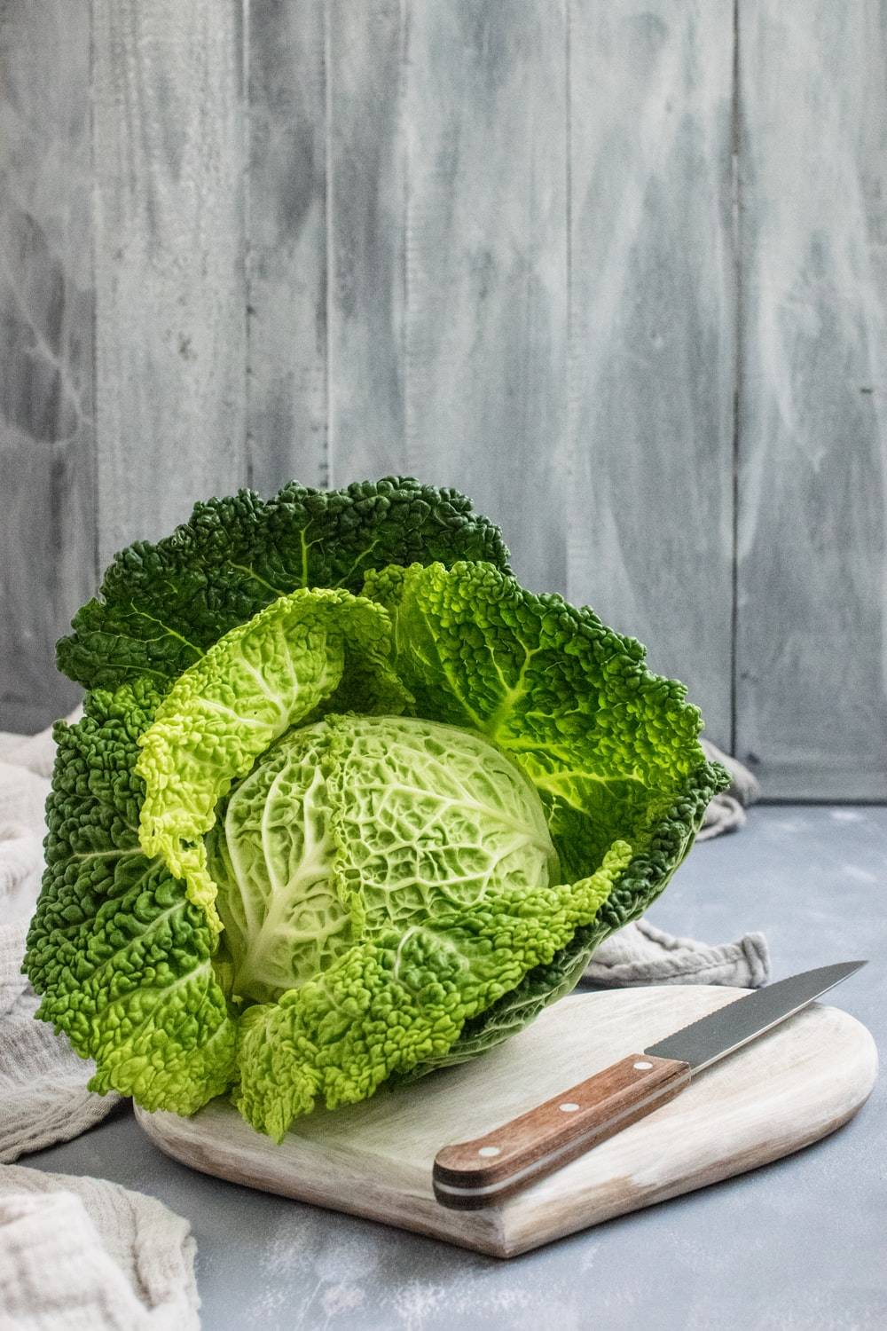 green cabbage on brown wooden chopping board