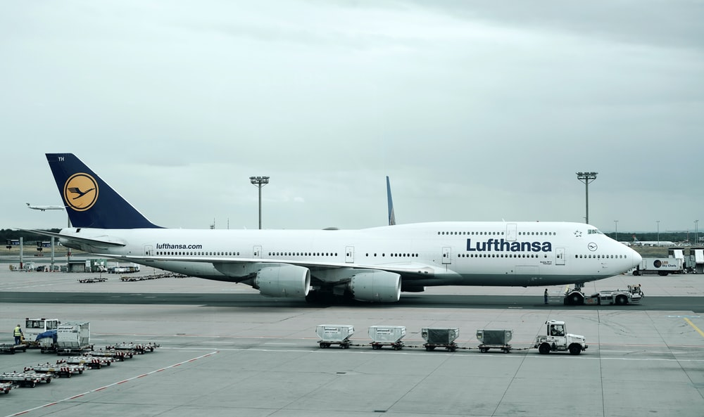 white and black Lufthansa airliner near vehicles