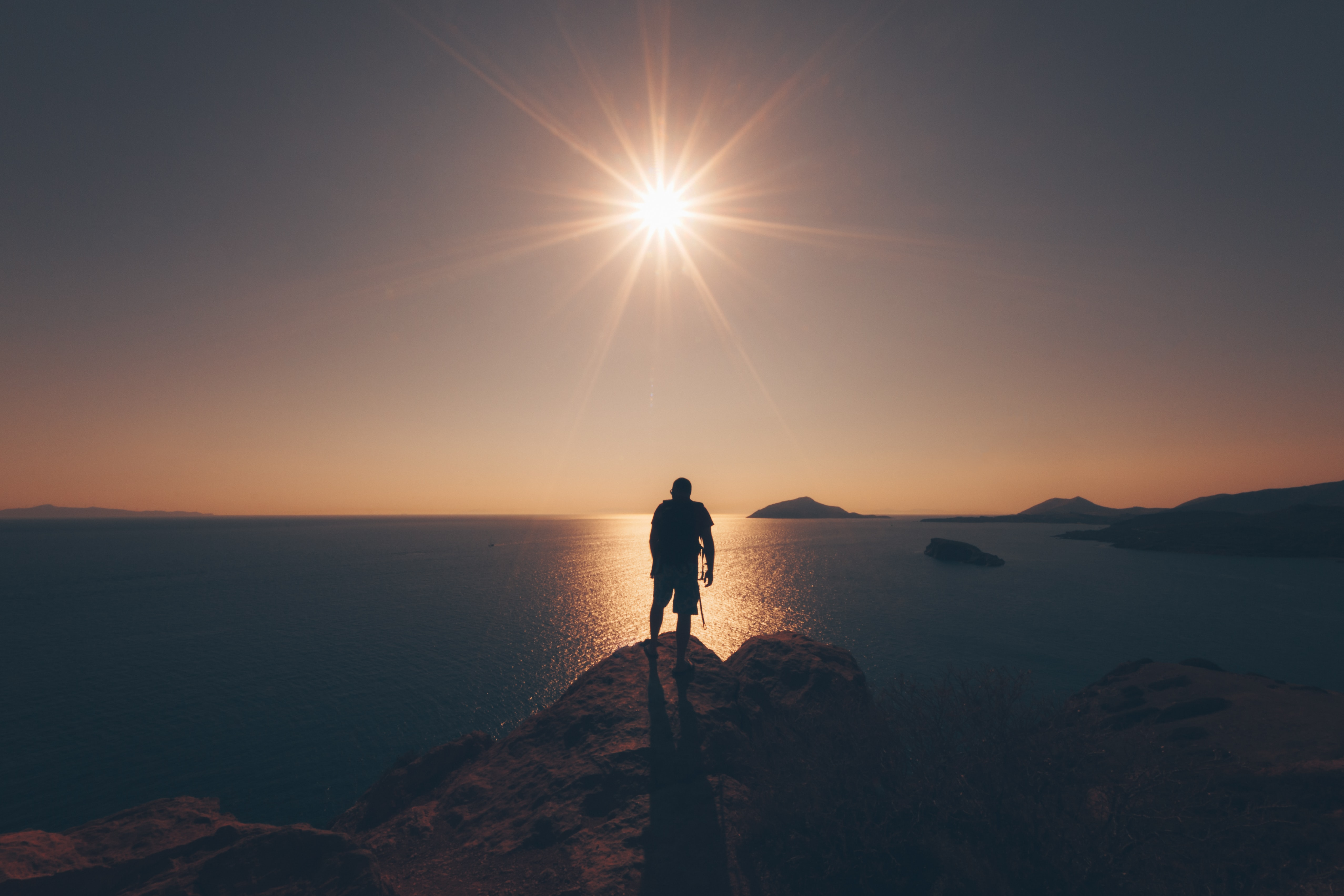 person standing on rock facing sea taken during golden hour