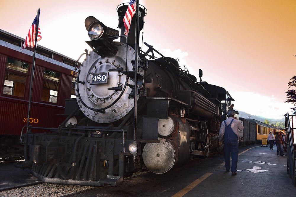 man walking beside locomotive train