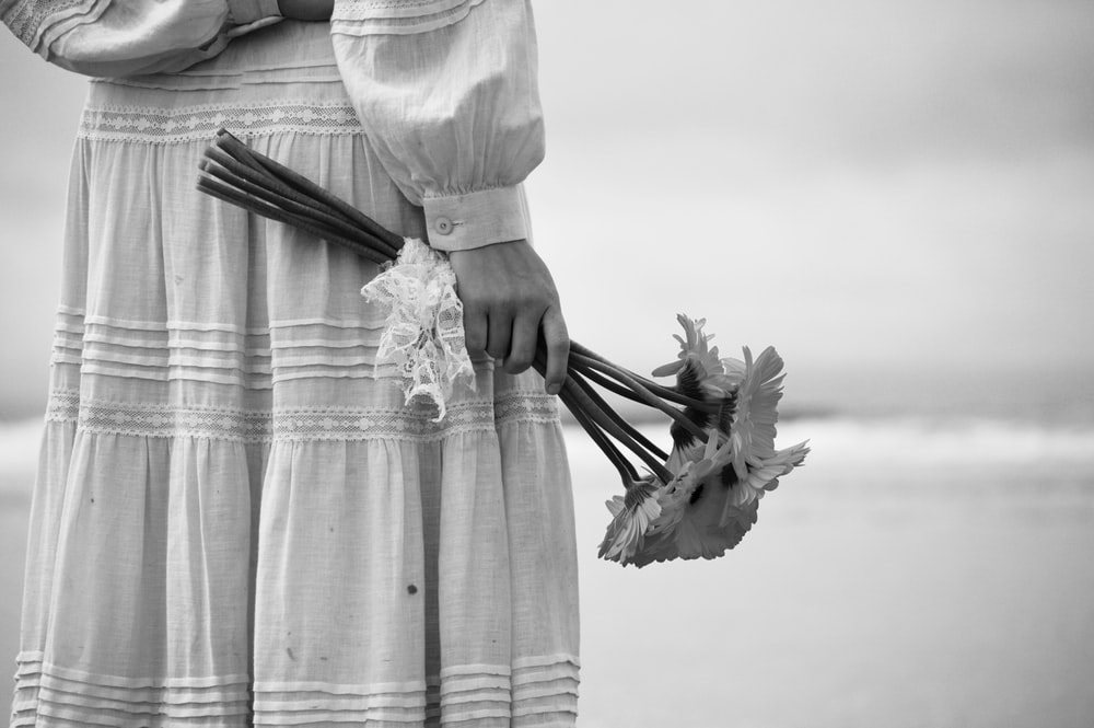 person holding bouquet of flowers at the beach