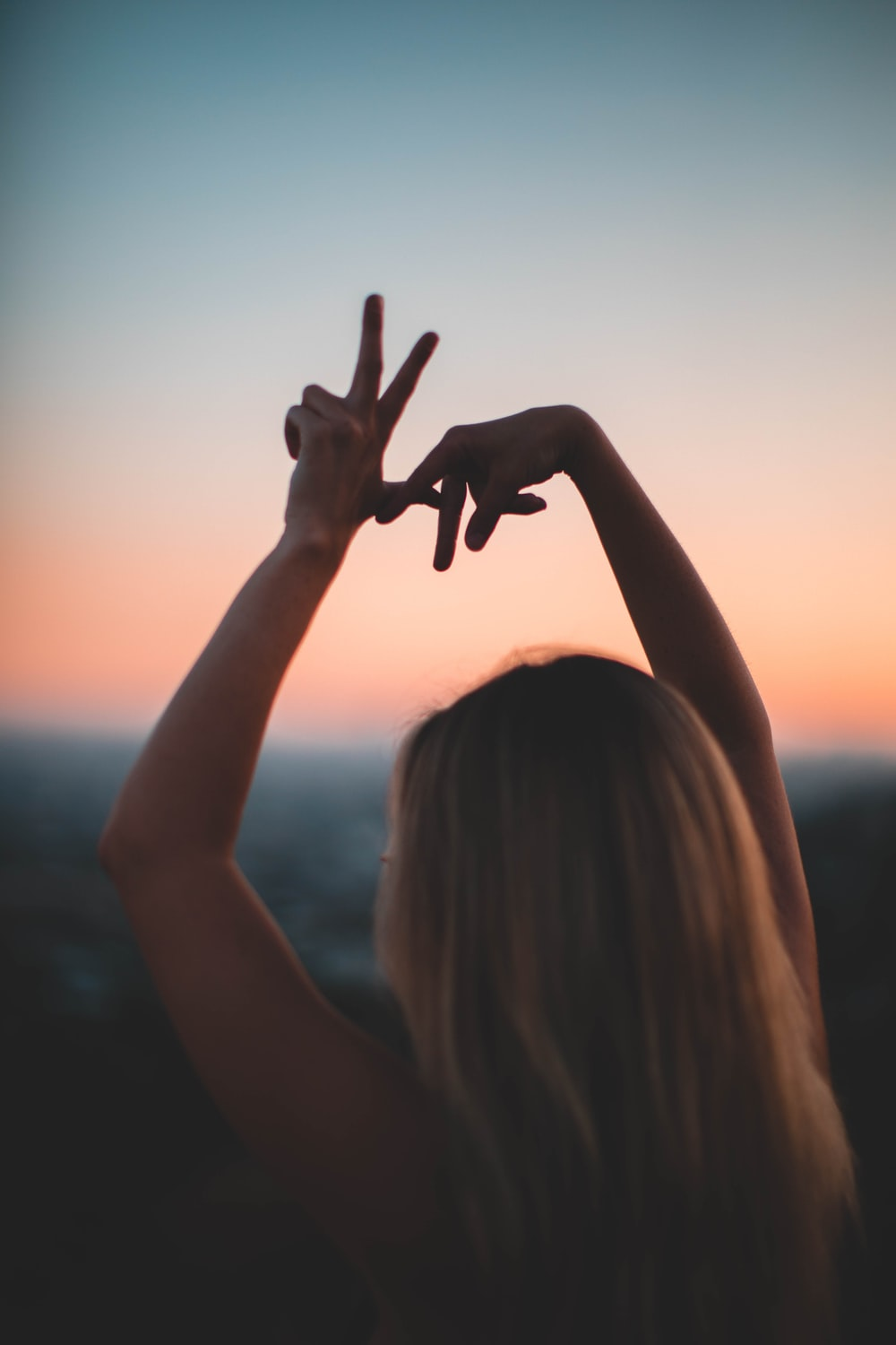 woman doing hand sign during golden hours