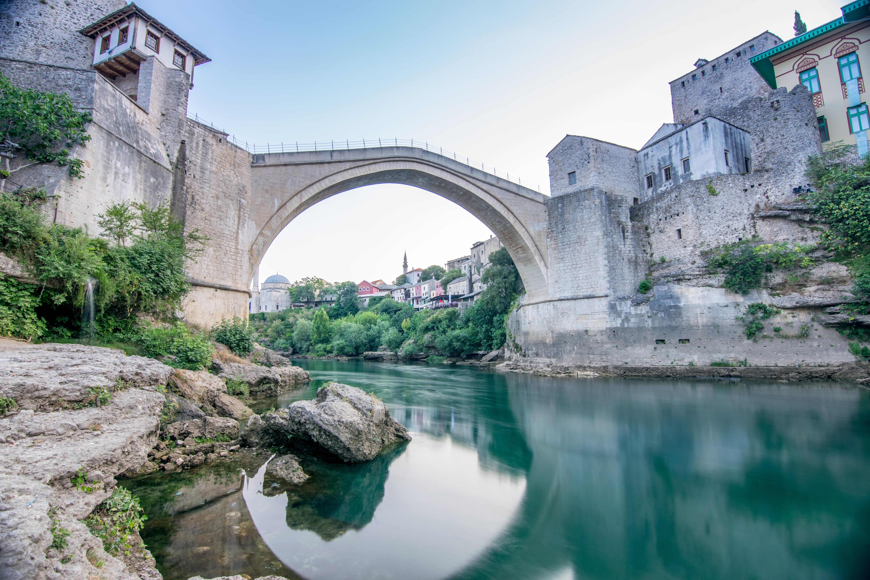 calm body of water under gray concrete bridge