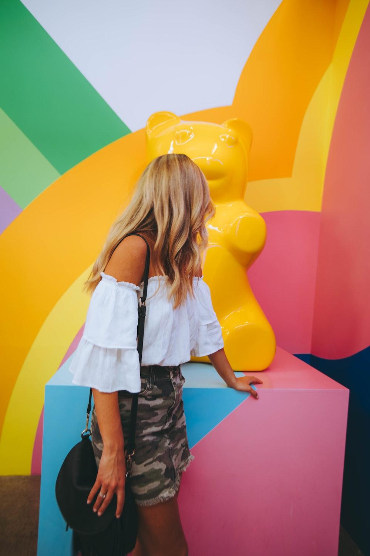 woman watching yellow bear sculpture